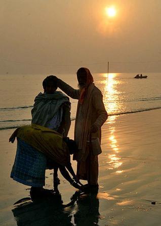 A sadhu blesses two women at Sagar island on Monday. Photo: Sushanta Patronobish